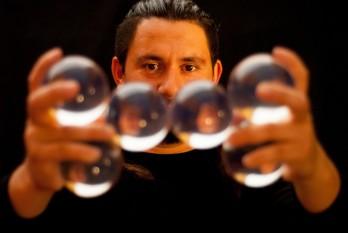 Mann mit Glaskugeln in den Händen.