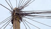 Das Bild zeigt einen Telefonmast mit unzähligen Drähten.