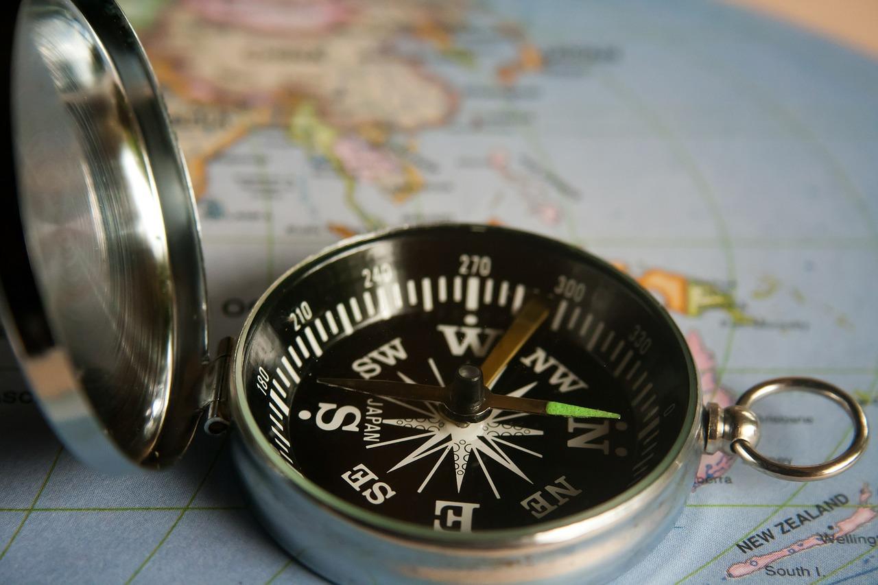 Kompass mit silbernem aufgeklapptem Deckel liegt auf einer Landkarte