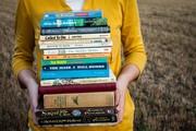 Eine Frau trägt einen Bücherstapel.