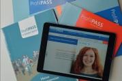 Das Bild zeigt ein Tablet, auf dem die Website des Profilpasses mit einem Frauenkopf und einem Kommentar zu sehen sind und mehrer Broschüren im Hintergrund zum Profilpass.