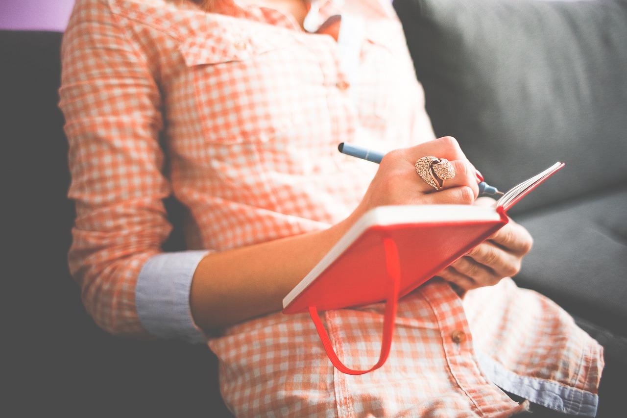 Eine Frau schreibt Eintragungen in ein Tagebuch.
