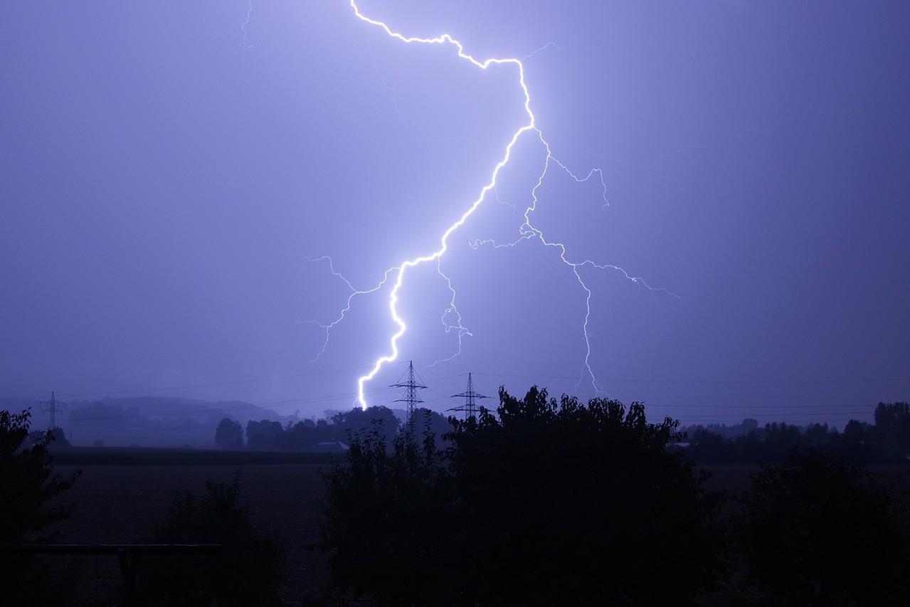 Landschaft im Dämmerlicht, ein Blitz zuckt über den Himmel