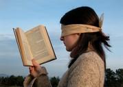 Das Bild zeigt eine Frau, die mit verbundenen Augen ein Buch anschaut.