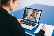Das Bild zeigt eine junge Frau mit Headset, die vor einem Laptop sitzt, auf der eine weitere Frau abgebildet ist, die etwas zeigt.