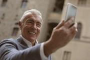Das Bild zeigt einen älteren Herrn, der lachend in sein Smartphone blickt.