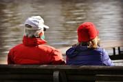 Das Bild zeigt ein älteres Paar, das auf einer Bank sitzt und auf einen See blickt.