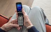 Ein klappbares Mobiltelefon in den Händen einer Seniorin