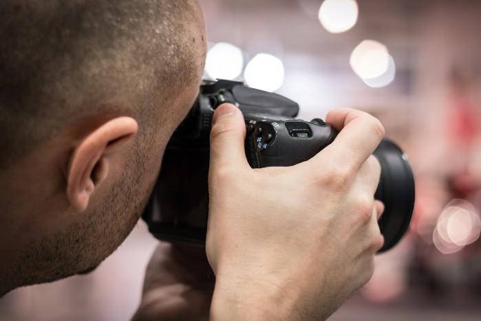 Mann fotografiert mit einer Digital-Spiegelreflexkamera