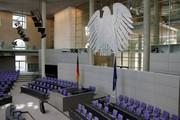 Das Bild zeigt einen Ausschnitt des Bundestages von innen mit Rednerpult, Reichsadler und Abgeordnetenplätzen.