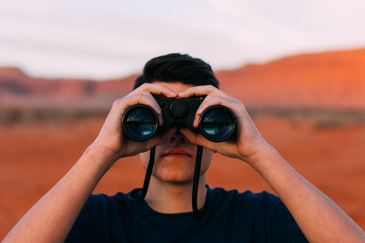 Mann in einer Landschaft schaut durch ein Fernglas.