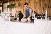 Das Bild zeigt einen Mann bei der Arbeit an eine rFrühstücks-/Kaffeebar.