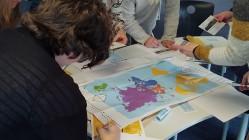 Das Bild zeigt einen Tisch, über den mehrere Menschen gebeugt sind. Auf dem Tisch sind eine bunte Weltkarte und verschiedene andere Karten, Stifte und Materialien zu sehen.