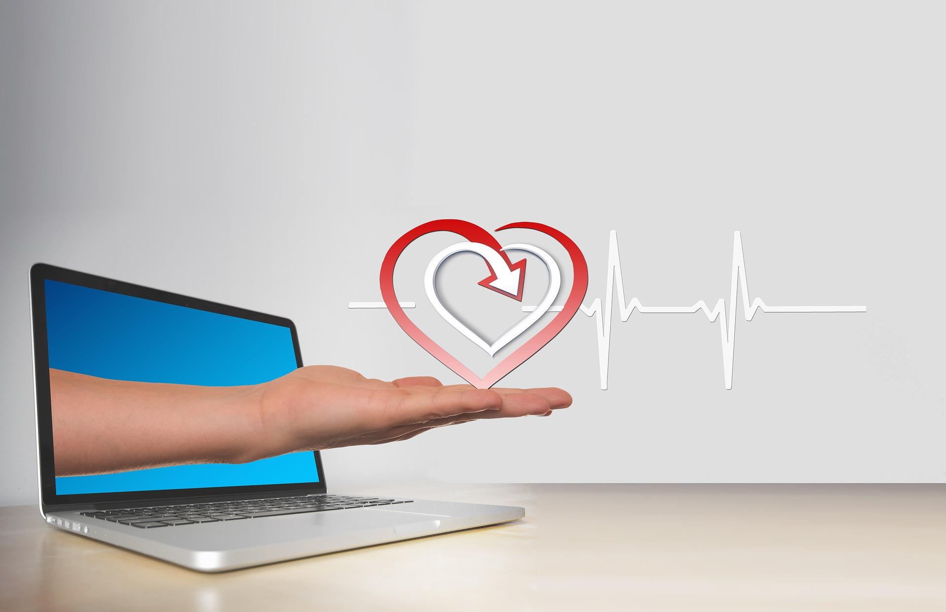 Das Bild zeigt einen Laptop, eine Hand mit einem Herz.