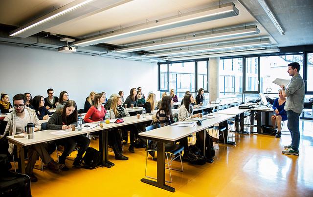 Seminarraum mit langen Tischreihen, alle schauen frontal nach vorne auf den Dozenten.