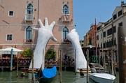 Das Bild zeigt ein Kunstobjekt in Venedig, zwei Hände greifen nach einem Haus.
