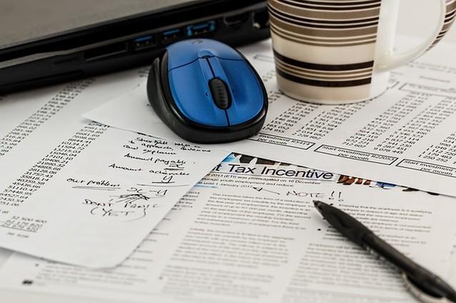 Auf einem Tisch liegen Blätter mit Texten und Zahlenreihen, eine Computermaus, ein Stift und eine Tasse.