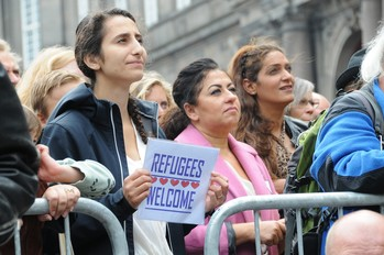 Menschen hinter einer Absperrung mit Schild mit Aufschrift Refugees Welcome