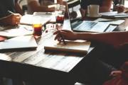Tisch mit Arbeitsmaterialien, Laptops, Gläsern; Arme von Menschen