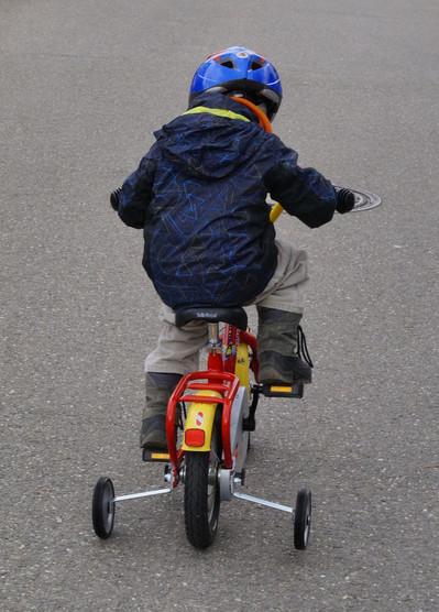 Ein Kind fährt auf einem Fahrrad mit Stützrädern