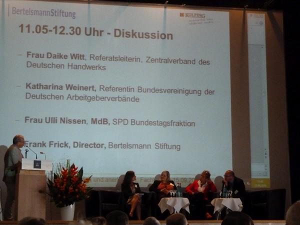 """Diskutanten der Veranstaltung """"Kompetenzen anerkennen""""auf einem Podium. Die Tagesordnung ist an die Wand projiziert."""