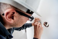Das Bild zeigt einen Elektriker, der eine Steckdose verlegt.