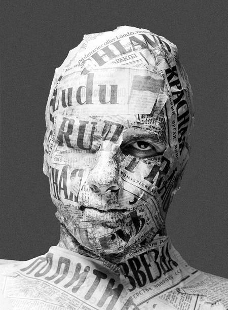 Ein Gesicht das komplett in Zeitungen eingehüllt ist. Man sieht nur das linke Auge des Mannes
