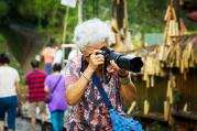 Das Bild zeigt eine reisende Seniorin mit Fotoapparat