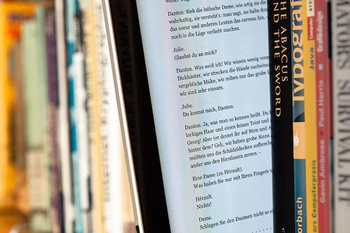 """Auf einem iPad ist der elektronische Text von Georg Büchners Drama """"Dantons Tod"""" zu sehen. Das iPad steht zwischen normalen Büchern in einem Regal."""