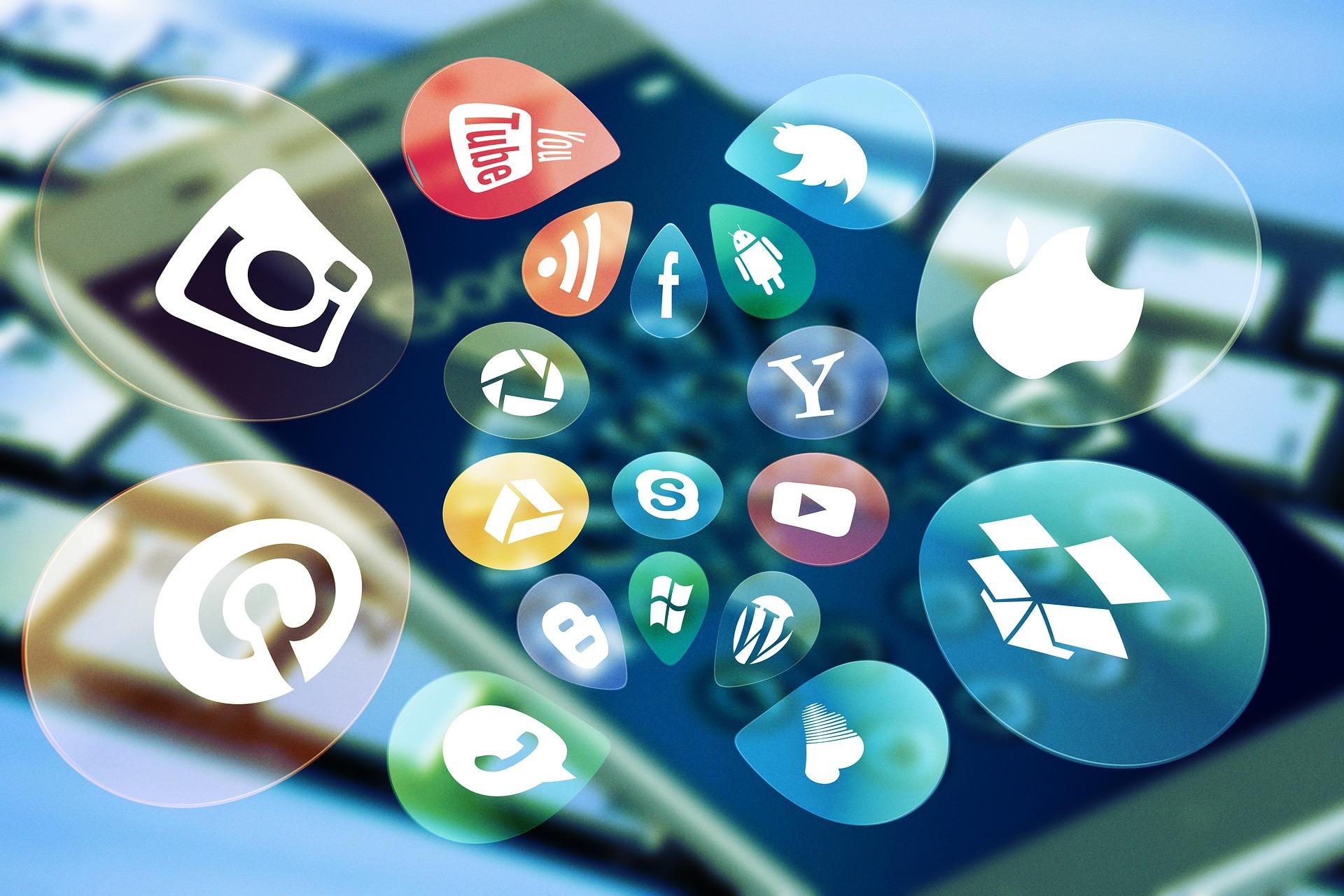 Das Bild zeigt im Hintergrund ein Smartphone und im Vordergrund diverse Social-Media-Icons.
