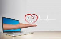 Das Bild zeigt im Hintergrund eine EKG-Kurce und im Vordergrund eine Hand, die aus einem Laptom ragt und ein grafisches Herz hält.