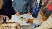 Das Bild zeigt den Spielekarton von Escape Climate Change mit mehreren Personen, die um den Karton herumstehen.