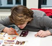 Das Bild zeigt eine Frau beim Lesen und Schreiben lernen.