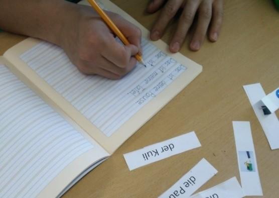 Person schreibt Vokabeln in ein Heft