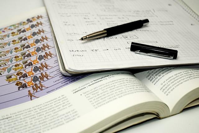 Das Bild zeigt ein offenes Lernbuch mit Notizblock und Stift.