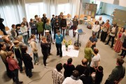 Das Bild zeigt eine Aufsicht auf einen Raum mit vielen verschiedenen Menschen, die alle in die Mitte gewandt jemand zuhören oder zuschauen.