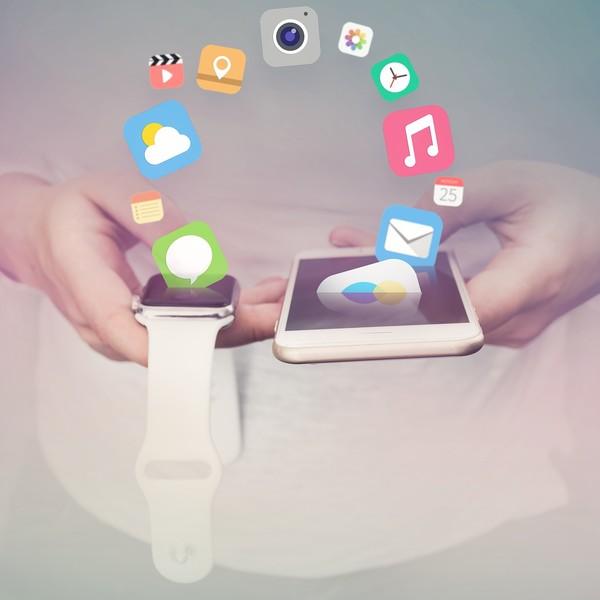 Ein Mann hält eine Smart Watch und ein Smartphone vor sich und zahlreiche Icons werden abgebildet die von einem Grät zum anderen schweben