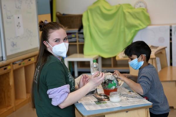 Das Bild zeigt eine junge Frau, die mit einem kleinen Jungen an einem Tisch etwas aus Pappmaché bastelt.