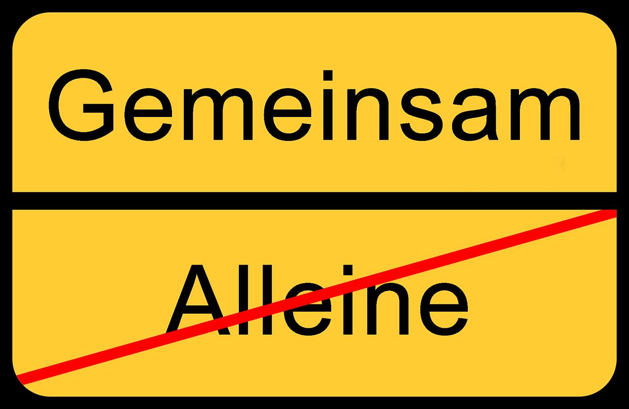 """Das Bild zeigt ein Schild auf dem """"Alleine"""" durchgestrichen ist und """"Gemeinsam"""" das Neue anzeigt."""